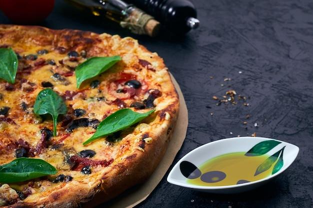 Italiaanse pizza en kookingrediënten op donkere achtergrond tomaten olijven olie kruiden en specerijen
