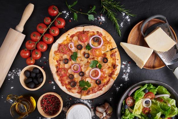 Italiaanse pizza en pizza kookingrediënten op donkere stenen ondergrond