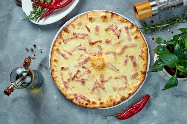 Italiaanse pizza met carbonara-saus, spek, parmezaan en eigeel. bovenaanzicht, voedsel plat