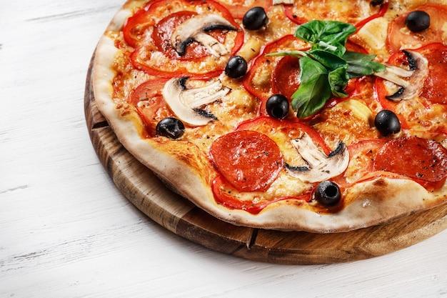 Italiaanse pizza met champignons, basilicum, tomaat, olijven en kaas