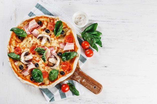 Italiaanse pizza met champignons, pepperoni, basilicum, tomaat, olijven en kaas