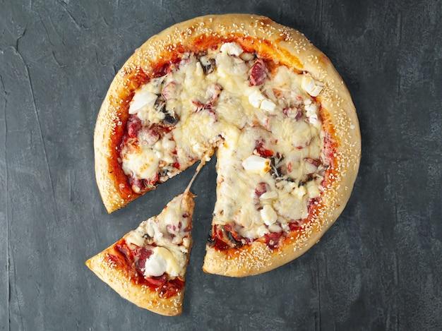 Italiaanse pizza met jachtworst feta kaas rode paprika champignons tomaat mozzarella kaas