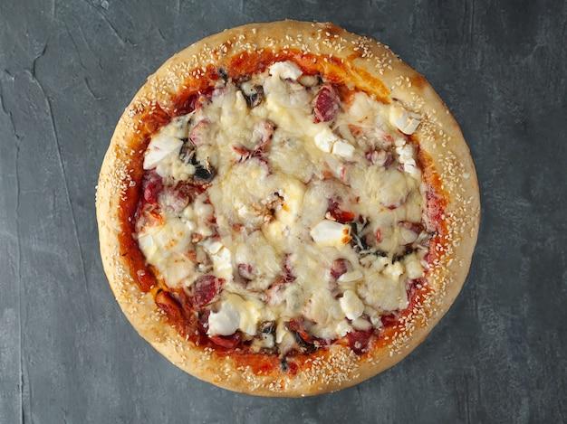 Italiaanse pizza. met jachtworst, fetakaas, rode paprika, champignons, tomaat, mozzarella kaas en tomatensaus. brede kant. uitzicht van boven. op een grijze betonnen achtergrond. geïsoleerd.