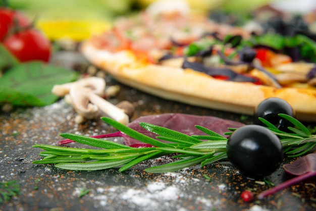 Italiaanse pizza met mozzarella, zwarte olijven, prosciutto en tomaten
