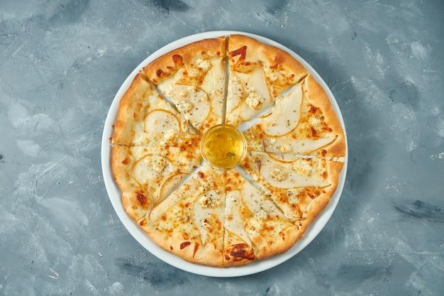 Italiaanse pizza met peer en gorgonzola-kaas op een witte plaat. betonnen ondergrond. bovenaanzicht