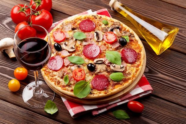 Italiaanse pizza met pepperoni, tomaten, olijven, basilicum en rode wijn op houten tafel. bovenaanzicht