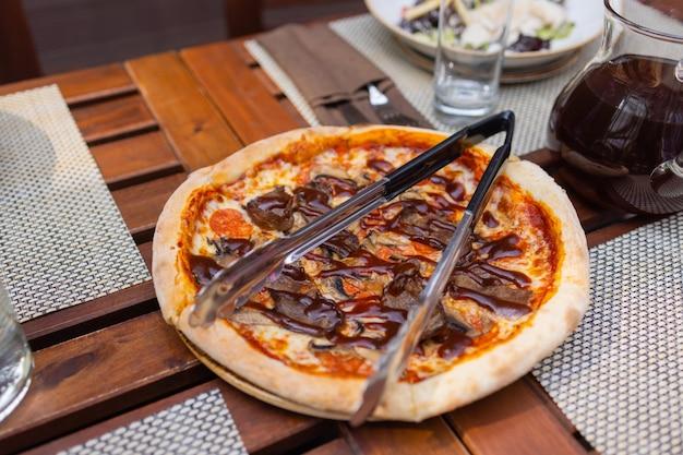 Italiaanse pizza met prosciutto tomaten olijven olijfolie parmezaanse kaas en rucola. wazig kleurrijk studioschot als achtergrond.