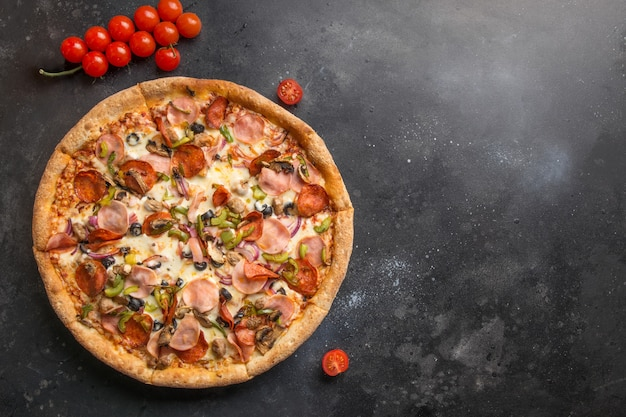 Italiaanse pizza met tomaat, champignons, pepperoni, ui, groene paprika, mozzarella kaas, saus