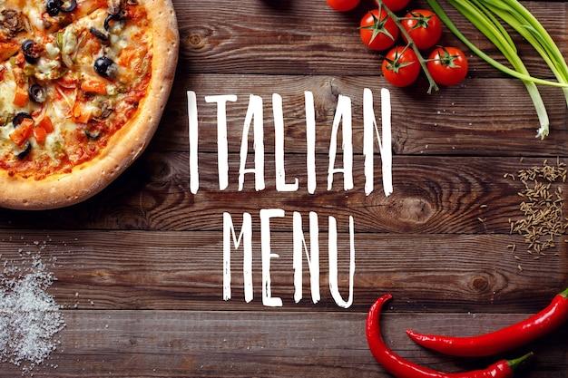 Italiaanse pizza met tomaten op een houten tafel, bovenaanzicht, close-up. tekst italiaans menu in het midden.