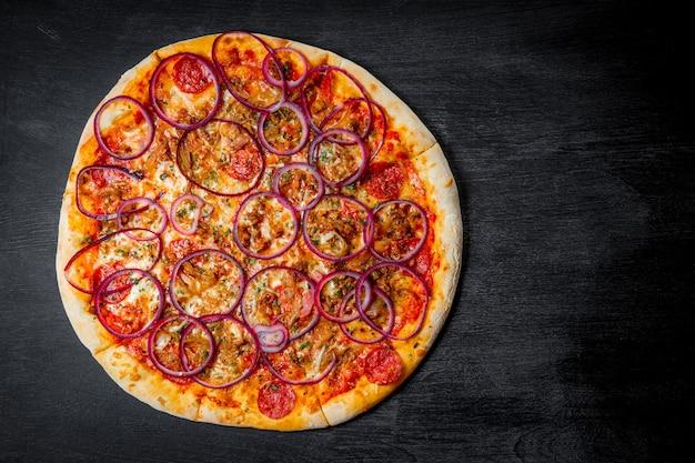 Italiaanse pizza met worst en uienringen op zwarte achtergrond, bovenaanzicht. hoge kwaliteit foto