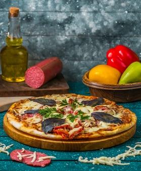 Italiaanse pizza met worst, paprika gegarneerd met donkere opaal basilicum en peterselie