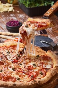 Italiaanse pizza op een houten tafel. een stuk hete pizza met kaas die zich uitstrekt.