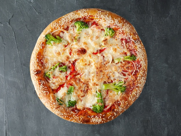 Italiaanse pizza vegetarisch. met broccoli, tomaten, uien, tomatensaus, mozzarella en sulguni. een brede kant. uitzicht van boven. op een grijze betonnen achtergrond. geïsoleerd.