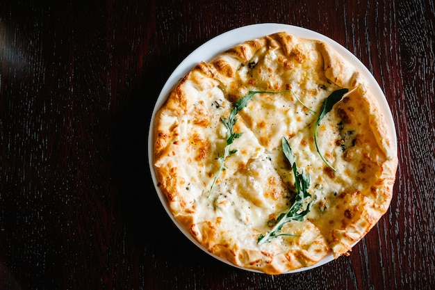 Italiaanse pizza vier kaas met rucola op een bruin houten bureau