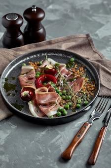 Italiaanse prosciutto crudo en jamon met rozemarijn. rauwe ham op beton grijs.