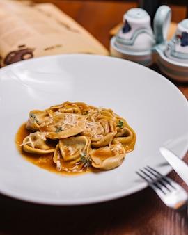 Italiaanse ravioli gegarneerd met geraspte parmezaanse saus en kruiden