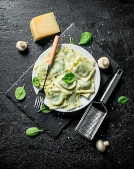 Italiaanse ravioli met champignons en spinazieblaadjes. op zwarte rustiek