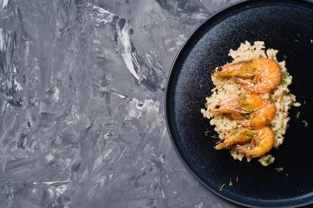 Italiaanse risotto met garnalen op een zwarte plaat.