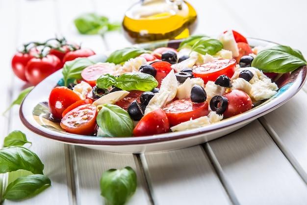 Italiaanse salade caprese van tomaten mozzarella kaas olijven basilicum en olijfolie.