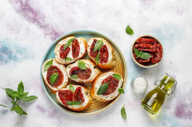 Italiaanse sandwiches - bruschetta met kaas, droge tomaten en basilicum.