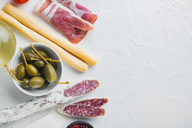 Italiaanse snacks, vleeskaas, kruiden set, op witte achtergrond, bovenaanzicht met kopie ruimte voor tekst