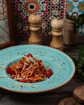 Italiaanse spaghetti in tomatensaus met muntblaadjes aan de bovenkant in een blauwe schaal