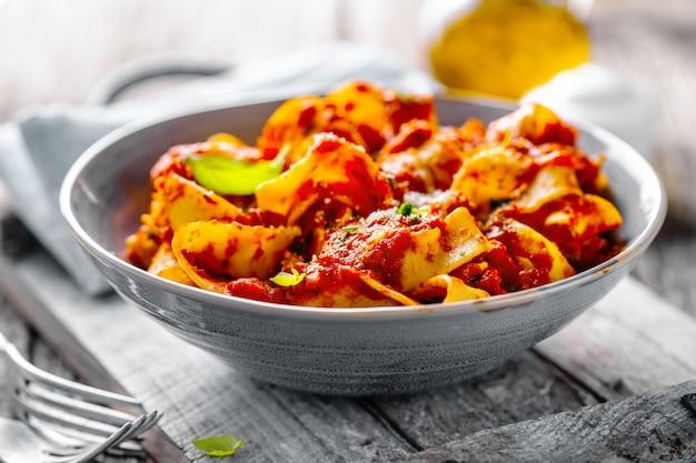 Italiaanse spaghetti met tomatensaus die op plaat wordt gediend