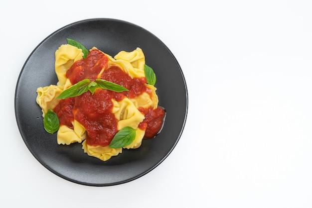 Italiaanse tortellinideegwaren met tomatensaus die op wit wordt geïsoleerd