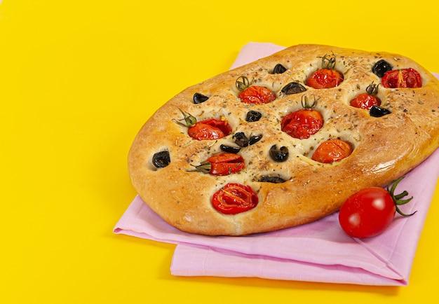 Italiaanse tortillafocaccia met tomaten, kruiden en olijven, op een felgele achtergrond.