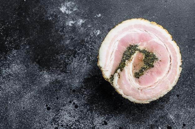 Italiaanse traditionele baconpancetta. zwarte achtergrond.
