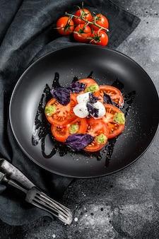 Italiaanse traditionele caprese salade. cherrytomaatjes, mozzarella kaas, basilicum, pestosaus. zwarte achtergrond. bovenaanzicht