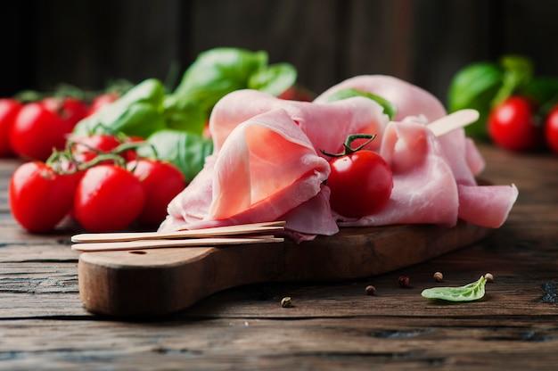 Italiaanse traditionele prosciutto met tomaat en basilicum op de houten tafel