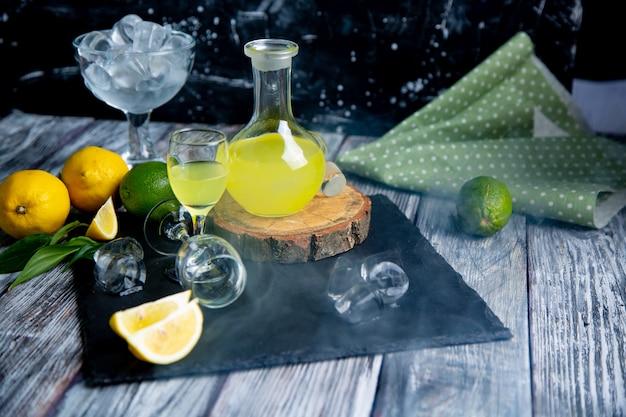 Italiaanse typische spijsverteringslimoncello met verse citroenen in rook, selectieve aandacht