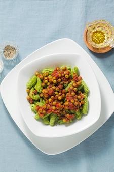 Italiaanse verse traditionele sardijnse pasta gnocchi met spinazie en doperwt tomatensaus. lente pasta voor paasvakantie.