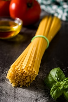 Italiaanse voedsel ruwe spaghetti met ingrediënten op zwarte achtergrond
