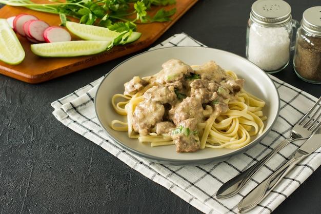 Italiaanse volkoren pasta met geroosterde kippenlever en uien geserveerd op een bord op marmeren achtergrond.