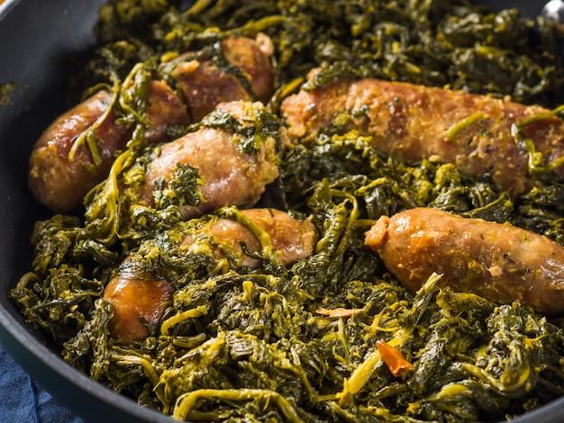 Italiaanse worsten met rapini-broccoli in een koekepan