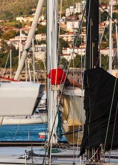 Italiaanse zeeman die aan boom van zeilboot werkt