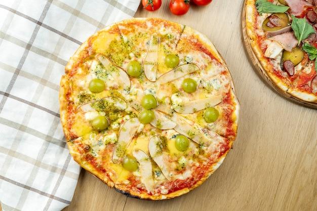 Italiaanse, zelfgemaakte 4 kaas pizza met peer en druiven op een houten tafel. bovenaanzicht eten met kopie ruimte. plat liggen