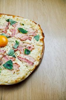 Italiaanse, zelfgemaakte carbonara pizza met dooier en spek op een houten tafel.