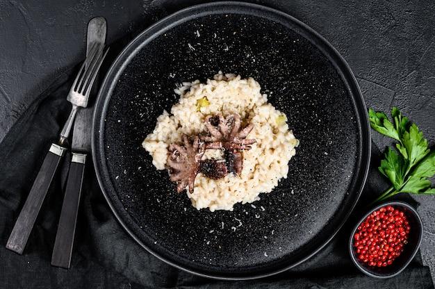 Italiaanse zelfgemaakte risotto met octopus en champignons, peterselie en kruiden. bovenaanzicht
