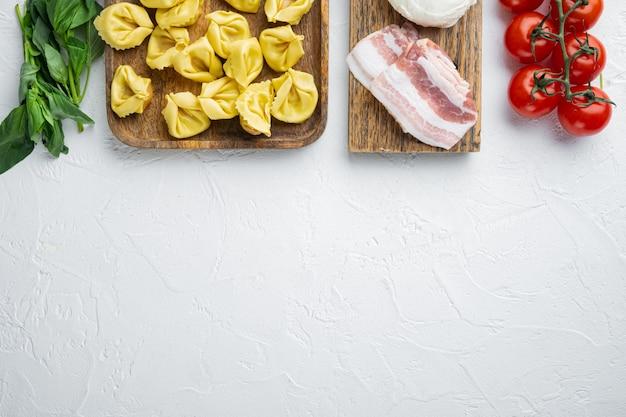 Italiaanse zelfgemaakte tortellini met ingrediënten, ham, basilicum, pesto, mozzarella set, op houten dienblad, bovenaanzicht plat