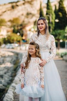 Italië, gardameer. stijlvolle moeder en dochter aan de oevers van het gardameer in italië aan de voet van de alpen. moeder en dochter in italië.