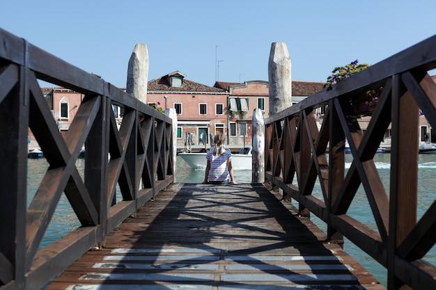 Italië, venetiaanse lagune, eiland murano. meisje met vlechten zit op de rand van een houten pier