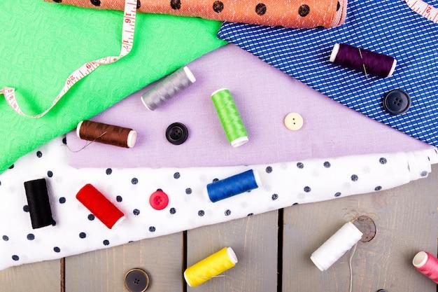 Items voor het naaien van kleding. naaien knoppen, spoelen van draad en doek. bovenaanzicht
