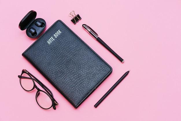 Items voor zakelijke persoon zwarte bril met notebook en pen trendy draadloze hoofdtelefoon op roze bac...