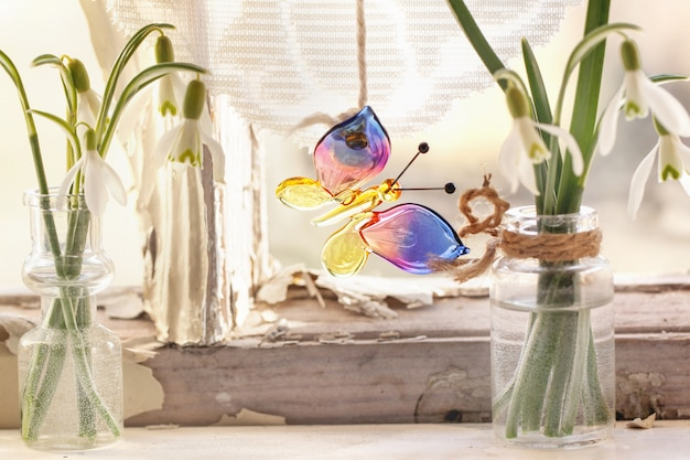 Iterieur venster met glazen vlinder en sneeuwklokjes