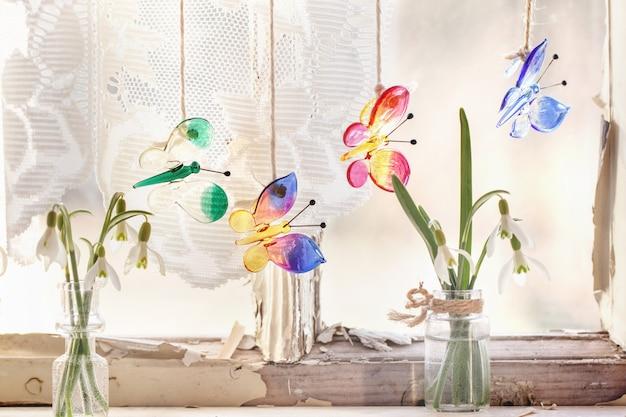Iterieur venster met glazen vlinders en sneeuwklokjes