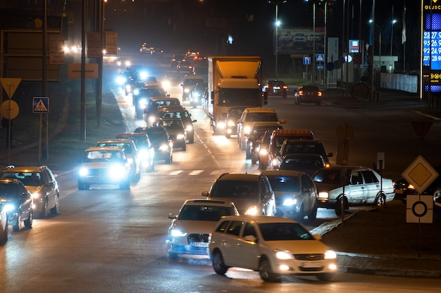 Ivano-frankivsk, oekraïne - 29 december 2020: verkeersopstopping met veel auto's die 's nachts langzaam op straat in de stad rijden.