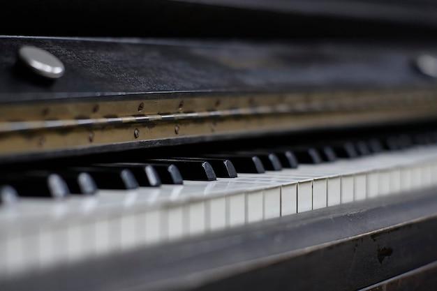 Ivoren toetsen van een antieke piano met de tekenen van tijd en slijtage.